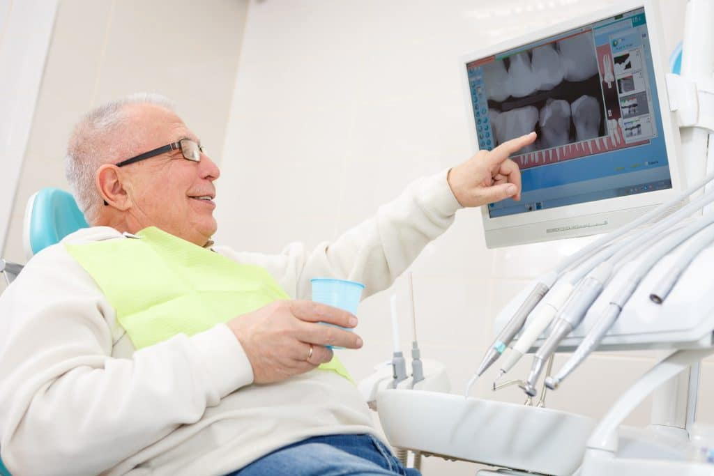 the smile doctor male dental patient looking at films